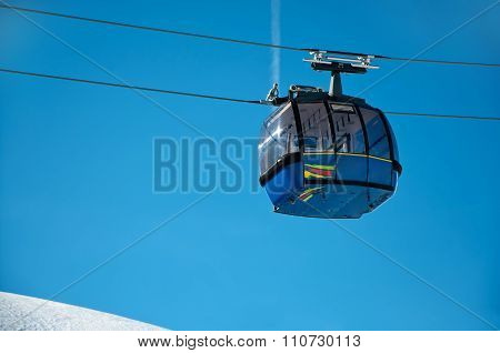 Blue Cabin Lift In Winter Resort With Copy Space And Blue Background