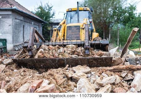 Bulldozer Demolishing An Old Building And Carrying Debris