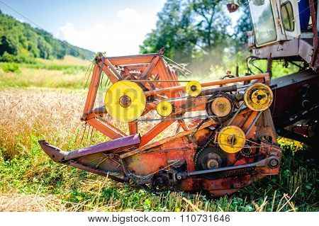 Detail Of Harvester Machinery, Tractor At Farm With Combine Collecting mature crops