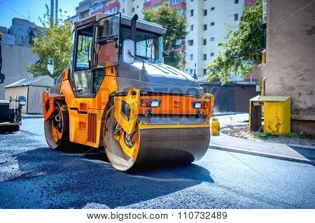 Heavy Tandem Vibratory Roller Compactor Working On Asphalt Pavement at road repairing