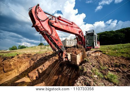 Excavator Loading Dumper Truck Tipper In Sandpit In Highway Construction site and quarry