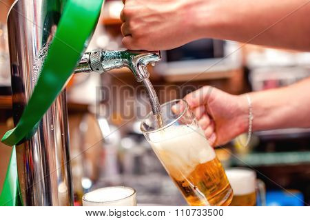Close-up Of Barman Brewing A Draft Beer At Pub. Bartender Pouring beer in a mug