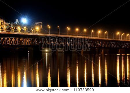 Railway bridge, 2 tiers, in the evening, lanterns are reflected in water.