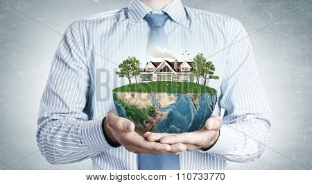 Close up of hands presenting model of green countryside life. Elements of this image are furnished by NASA