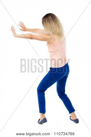 back view of woman pushes wall. Isolated over white background. Rear view people collection. backside view of person.The blonde in a pink jacket repels hand wall.