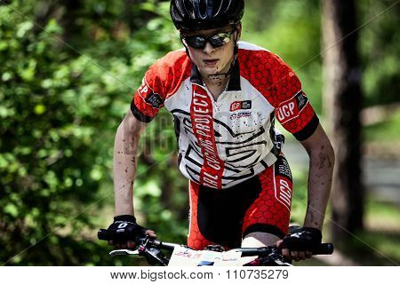 young man athlete cyclist rides through forest. face and hands in dirt