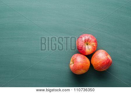 red apples on green chalkboard