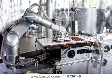 Automatic Robotic Hand Moving And Preparing Tiny Bits Of Chocolate at factory