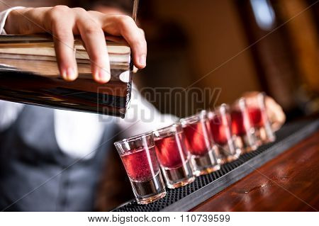 Close-up Of Barman Hand Pouring Alcohol Into Shot Glasses In A Nightclub