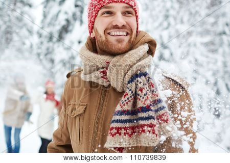 Happy guy in winterwear on background of his friends