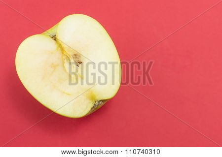 Halved Green Apple On Red Background