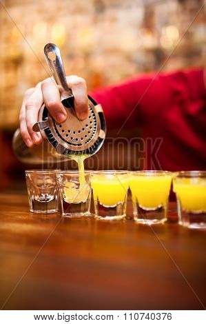 Bartender Pouring Strong Alcoholic Drink Into Small Glasses On Bar