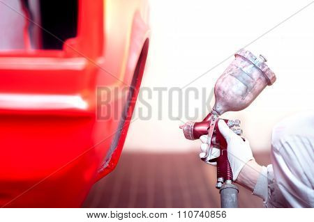 Worker Painting A Red Car Or Element In A Special Garage, Wearing a white costume