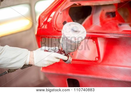Close-up Of Spray Paint Gun Painting A Red Car In Painting Booth