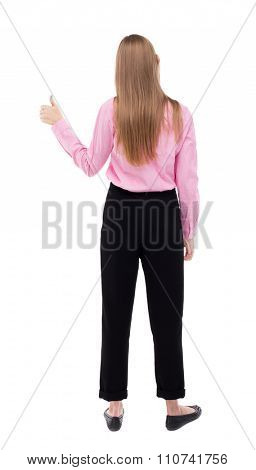 Back view of  woman thumbs up. Rear view people collection. backside view of person. Isolated over white background. The girl office worker in black trousers shows thumb up with his left hand.