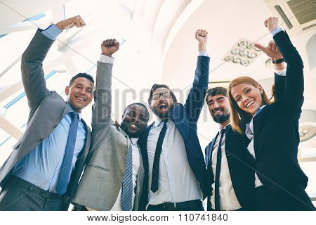 Ecstatic business partners raising their arms and looking at camera