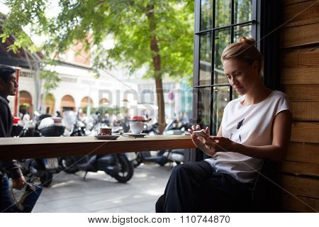 Attractive woman reading text message on cell telephone while sitting in cozy coffee shop