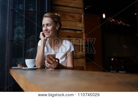 Beautiful woman with cute smile holding smart phone while sitting in cafe during her recreation time
