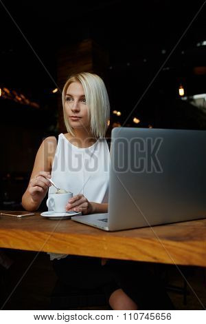 Young charming dreamy Caucasian woman sitting with portable net-book in cafe during coffee break
