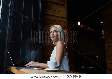Thoughtful attractive female freelancer using portable net-book for distance work