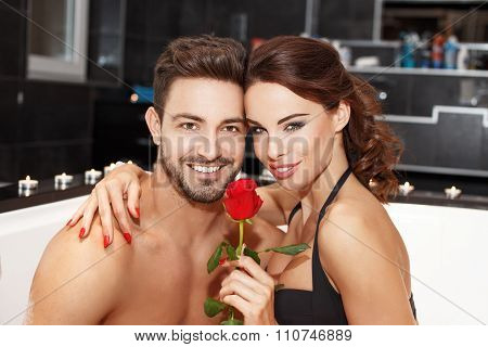 Happy Young Couple In Jacuzzi With Rose