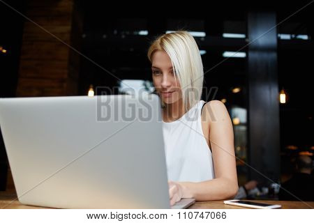 Beautiful blonde female student working on laptop computer before her lectures in University