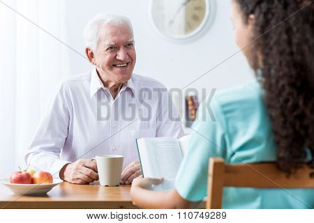 Retiree And Nurse Reading Book
