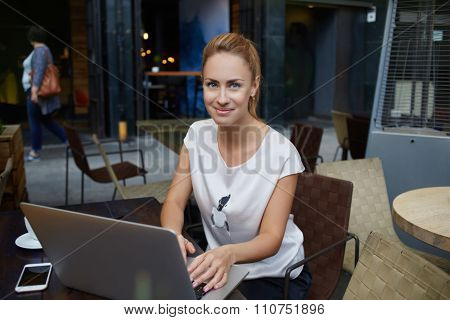 Portrait of a beautiful lady sitting at the table of sidewalk cafe with open laptop computer