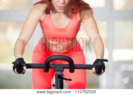 Close-up, Woman Training On Cycling Machine In Fitness Center
