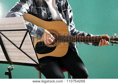 Musician plays guitar on blue background in studio with musical notes holder, close up