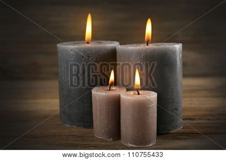Alight wax grey candle on wooden background