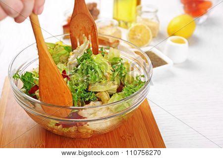 Young man preparing healthy salad, close-up