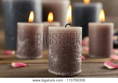 Alight wax grey candle with flower petals and pebbles on wooden background