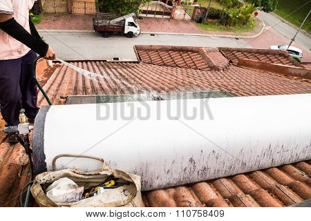 Worker Cleaning Solar Water Heater On Roof During Maintenance