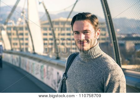 Handsome young man walking in city with backpack