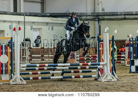 woman athlete rider horse overcomes obstacles sports complex indoors