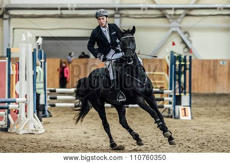 male rider on horse galloping across field sports complex