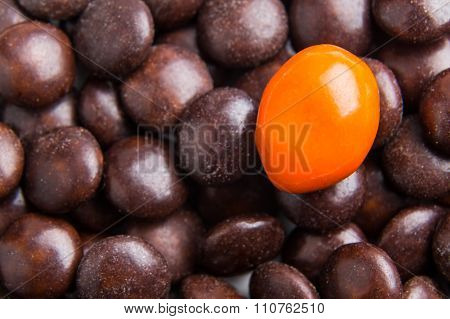 Focus On Orange Chocolate Candy Against Heaps Of Brown Candies