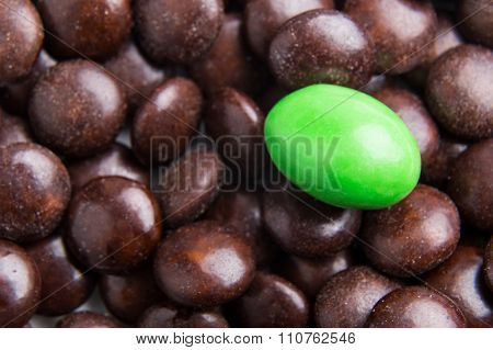 Focus On Green Chocolate Candy Against Heaps Of Brown Candies