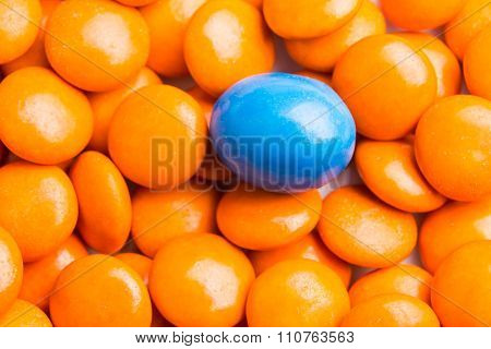Focus On Blue Chocolate Candy Against Heaps Of Orange Candies