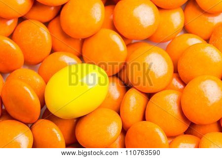 Focus On Yellow Chocolate Candy Against Heaps Of Orange Candies