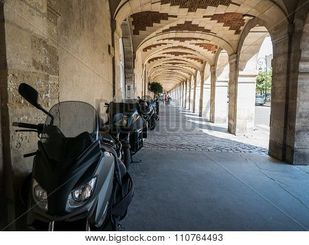 Motorscooters Parked Under Place Des Vosges Arcade, Paris