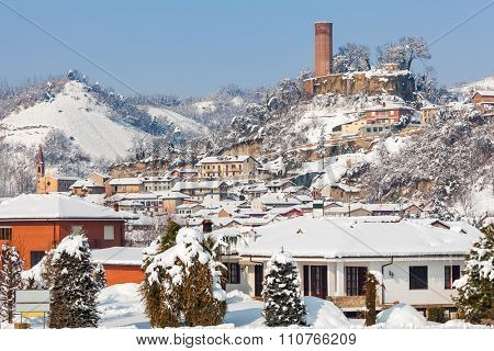 Small town covered with snow in sunny day in Piedmont, Northern Italy.