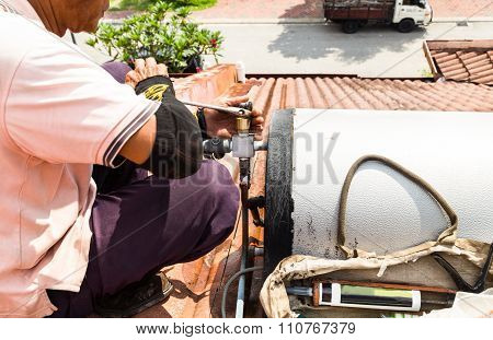 Closeup Worker Fixing Solar Water Heater On Roof During Maintenance