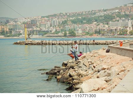 People Fishing On A Bay Of Aegean Sea At Sunny Day In Modern City