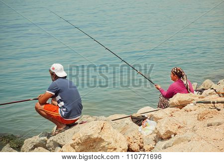 Woman With Rod And Man Fishing On A Bay With Blue Water Of Aegean Sea