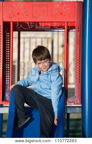 Playground in winter sunny day. Beautiful six year old boy on a children's slide