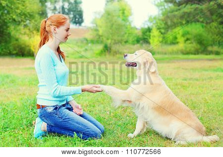 Happy Owner Woman Training Golden Retriever Dog On Grass In Park, Giving Paw