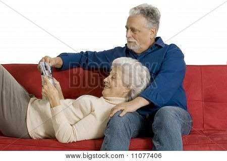 elderly couple on the couch reading a magazine