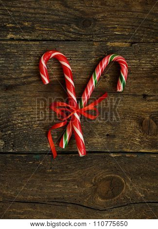 Closeup Of Two Old Fashioned Candy Canes On A Rustic Wooden Background